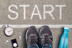 Men Running shoes and equipment on asphalt whit start inscription. Running training on hard surfaces. Runner Equipment stopwatch a. Nd music player and plastic Royalty Free Stock Photos
