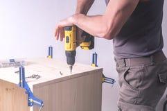 Men& x27; s工作:一个人与螺丝刀一起使用 聚集内阁家具由木头制成 图库摄影