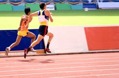 Men's 100 Meters for Blind Persons. A blind athlete competing in a Men's 100 meters race. The blind athlete is seen here running in tandem with his guide Royalty Free Stock Photo