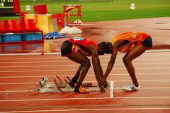 Men's 400m T11 athletics final. Amando Jose of Angola, left, is adjusted the hand position for starting line by his guide before the  Men's 400m T11 at the Stock Photos