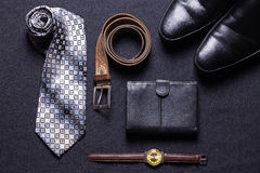 Men`s accessories on black background tie wallet watch strap sho. Es Stock Image