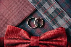 Men`s accessories - bow tie, wedding rings on textile background. Stock Images