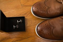 Men`s accessories. Brown leather shoes and silver cufflinks in a box on a wooden background. details. Men`s accessories. Brown leather shoes and silver cufflinks Royalty Free Stock Photography