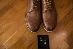 Men`s accessories. Brown leather shoes and silver cufflinks in a box on a wooden background. Groom details Stock Image