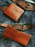 Men`s accessories. Brown leather wallet. Brown leather wallet on jeans background royalty free stock image