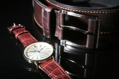 Men`s accessories for business and rekreation. Leather belt, Watch, notepad and pen on black mirror background. Top view. Composition royalty free stock photo