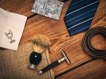 Men`s accessories lying on wood desk. Men`s accessories cufflinks, tie, razor, shaving brush, card, belt lying on wood desk Stock Photos
