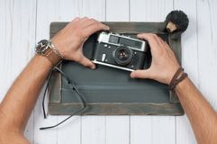 Men`s accessories. Men`s hands holding camera. On wooden background Stock Photo