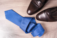 Men`s accessories men`s shoes, tie on a wooden background. Classic men`s accessories. Top view. Copy space for text Stock Image