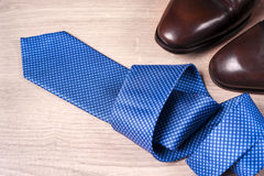 Men`s accessories men`s shoes, tie on a wooden background. Classic men`s accessories. Top view. Copy space for text Royalty Free Stock Photography