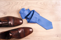 Men`s accessories men`s shoes, tie on a wooden background. Classic men`s accessories. Top view. Copy space for text Royalty Free Stock Images