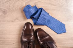 Men`s accessories men`s shoes, tie on a wooden background. Classic men`s accessories. Top view. Men`s accessories men`s shoes, tie on a wooden background Stock Images
