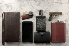 Men`s Accessories. men`s style. Smartphone, wallet, flask, keys, business card, and perfume on a light concrete background. flat stock images