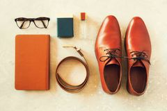 Men`s accessories and shoes on gray background. Flat lay of elegant belt, glasses, parfume, notebook. Stylish set and. Fashion concept for man Stock Photography