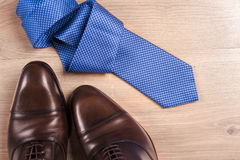 Men`s accessories men`s shoes, tie on a wooden background. Classic men`s accessories. Top view. Men`s accessories men`s shoes, tie on a wooden background Royalty Free Stock Photography