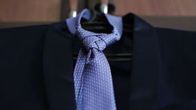 Men's accessories tie and jacket hanging on a hanger stock footage