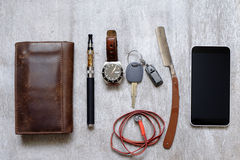 Men's Accessories , top view on a wooden wallet the phone purse, razor and e-cigarette Stock Photos