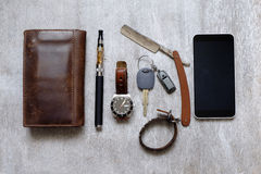 Men's Accessories , top view on a wooden wallet the phone purse, razor and e-cigarette Royalty Free Stock Photos