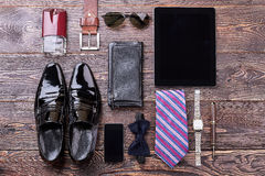 Men`s accessories on wooden background. Black shoes and bow tie. Expensive look for man Stock Images
