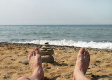 Men's bare feet on background of sea. And stones Stock Photos