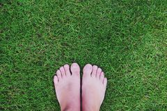 Men`s bare feet on green grass royalty free stock photo