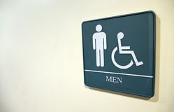 Men's bathroom sign on white wall with handicapped symbol. Men's bathroom symbol on white wall, with room for text space, with handicapped symbol royalty free stock photos