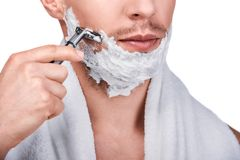 Men`s beauty. Handsome man shaving. Men`s beauty. Cropped image of handsome man shaving with a razor, isolated on white royalty free stock images
