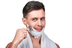 Men`s beauty. Handsome man shaving. Men`s beauty. Portrait of handsome man shaving with a razor and smiling, isolated on white royalty free stock image