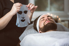Men`s biocellulose mask treatment at spa. Man during moisturizing biocellulose mask treatment at beautician`s Royalty Free Stock Photos