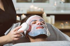Men`s biocellulose mask treatment at spa. Man during moisturizing biocellulose mask treatment at beautician`s Stock Image