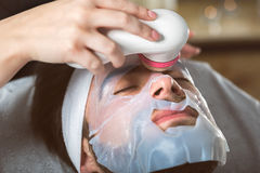 Men`s biocellulose mask treatment at spa. Man during moisturizing biocellulose mask treatment at beautician`s Stock Photo