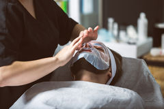 Men`s biocellulose mask treatment at spa. Man during moisturizing biocellulose mask treatment at beautician`s Royalty Free Stock Photography