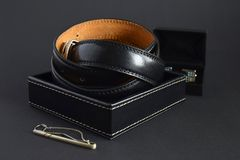 Men`s black leather belt in box, silver tie clip and cufflinks. royalty free stock image