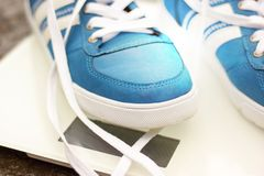 Men`s blue sneakers on a white square scales on the asphalt road, autumn. Close-up Stock Photos