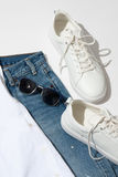 Men`s blue sunglasses on jeans. Men`s blue sunglasses laying on jeans near white sneakers Royalty Free Stock Images