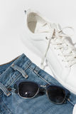 Men`s blue sunglasses on jeans. Men`s blue sunglasses laying on jeans near white sneakers Royalty Free Stock Photo