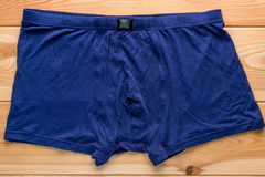 Men`s briefs boxers from the blue color cotton. On a wooden floor closeup Stock Photos