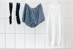 Men`s briefs socks and shirts weigh in the bathroom on the rope. To dry. Linen for every day of the week, linens for every day, bachelor panties, family panties stock photos