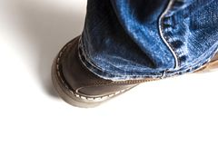 Men`s brown boots and blue jeans isolated. Men`s brown boots and blue jeans. Isolated on white bacground royalty free stock photography