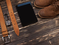 Men`s brown clothing and accessories set: boots, leather belt, watch pc-tablet. Men`s brown clothing and accessories set: boots, leather belt, watch and pc Royalty Free Stock Images