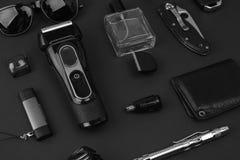Men`s casual accessories on stone background. Watch, screwdriver, knife, glasses, USB stick, car keys, purse, electronic cigarett