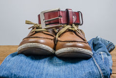 Men's casual jeans and brown leather belt with leather shoe. On wooden board Stock Photography