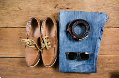 Men's casual jeans and brown leather belt with leather shoe. On wooden board Royalty Free Stock Photos