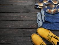 Men`s casual wear, yellow work boots from natural nubuck leather, blue jeans, checkered shirt and brown belt on dark wooden. Background top view flat lay copy royalty free stock images