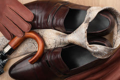 Men's classic accessories: brown shoes, tie, umbrella and gloves on a wooden surface. Top view Stock Images