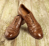 Men`s classic brown leather shoes on the wood floor. Royalty Free Stock Photo