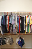 Men's Clothes in a Closet. Casual menswear of dress shirts, polo shirts, t-shirts, short pants and gym shorts hanging neatly in a walk in closet of a home Royalty Free Stock Photo