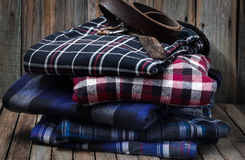 Men's clothes on wooden background. Men's clothes, neatly stacked on wooden background Stock Images