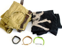 Men`s Clothing. Flat Lay Composition of Men`s Pants with Belt, Pile of T-Shirts, Watch and two Bracelets Royalty Free Stock Photos