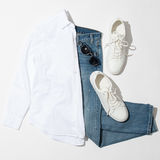 Men`s clothing set. Men`s blue sunglasses laying on jeans near white sneakers and shirt Stock Image